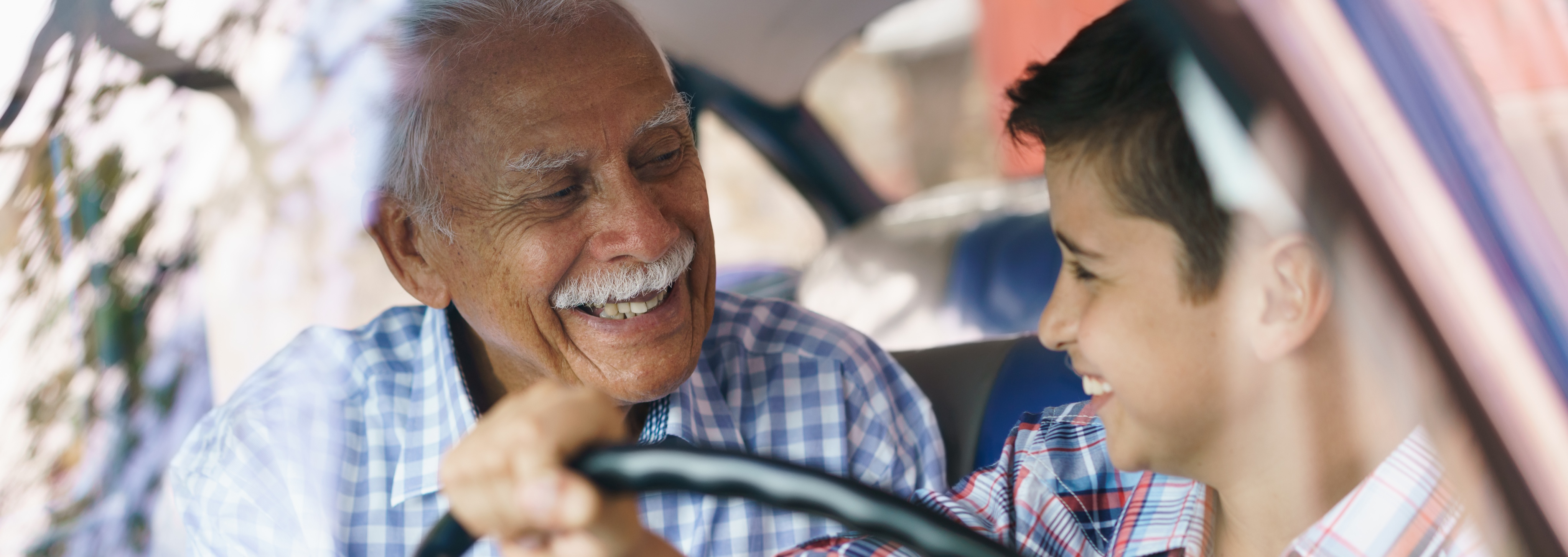 Family and Generation gap. Old grandpa spending time with his grandson and teaching him to drive. The boy holds the volante of a vintage car from the 60s. They both smile happy looking each other.